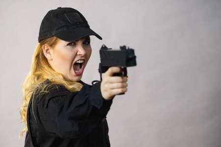 La mujer sostiene la pistola automática en las manos. Ejército, arma.