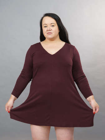 Curvy woman showing showing plus size of brown long cotton elastic dress tunic. Mature fashion, clothing, style concept.