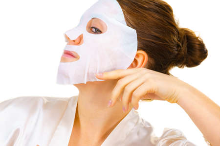 Woman applying sheet mask on her face, on white. Girl taking care of skin complexion. Beauty treatment. Skincare. Фото со стока