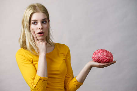 Young woman female student thinking about solving problem, holding fake brain. Stockfoto