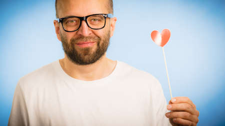 Adult man wearing eyeglasses being in love holding small red shape heart on stick. Romance, flirting, Valentines Day concept.