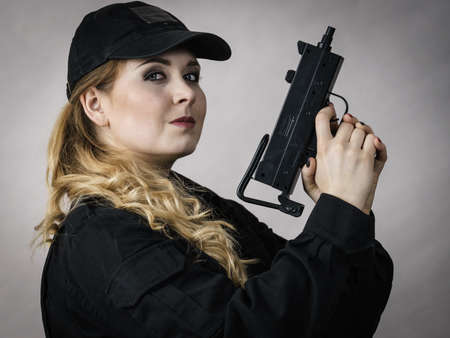 Woman holds automatic gun in hands. Army, weapon.