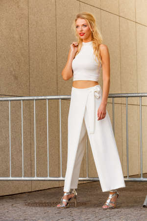 Fashion model woman wearing white outfit with crop top and wide trousers culottes.