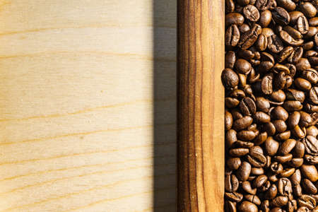 Roasted brown coffee beans in wooden frame.