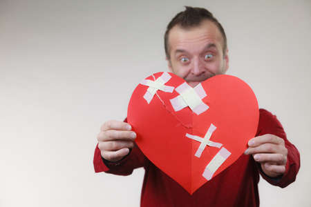Bad relationships, breaking up, emotions concept. Funny adult man holding broken heart, on grey Stockfoto