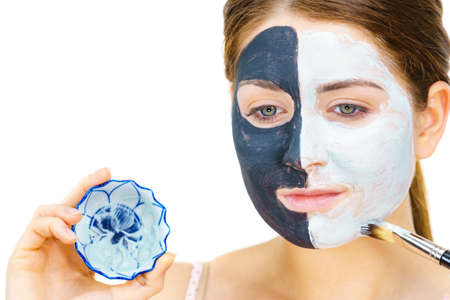 Woman with clay carbo black mask on half face applying white mud to clean skin. Girl taking care of oily complexion. Beauty procedures. Skincare. 版權商用圖片
