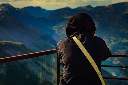 Tourist standing on Dalsnibba viewpoint, Geiranger Skywalk platform, enjoying mountains view, Norway.