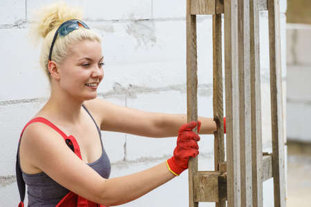 Woman about to do some work on construction site holding wooden Euro pallets