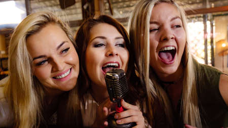 Women singing songs in karaoke club. Female friends with microphone having fun. Party, celebration, nightlife and people concept. Banco de Imagens