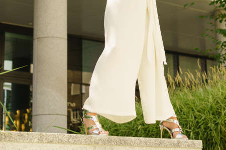 Elegant unrecognizable woman presenting fashionable urban outfit. White crop top and trousers culottes.