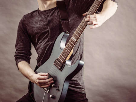 Unrecognizable male person with electric guitar. Close up, part body guy is holding instrument and playing. Hobby, music concept Stock Photo