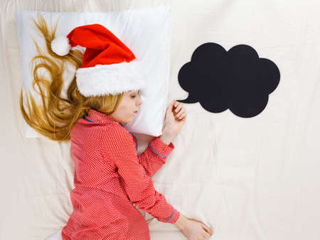 Sleeping woman waiting for Christmas season wearing pajamas and Santa hat lying in bed dreaming about celebrating holiday