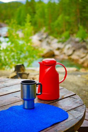 Picnic site table with flask and thermal mug, norwegian mountains nature in the background. Stok Fotoğraf