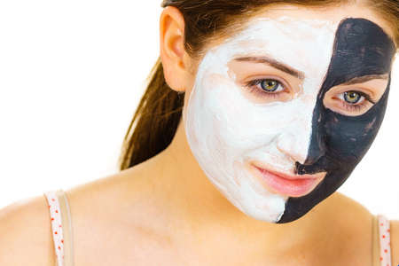 Woman with clay carbo black mask on half face applying white mud to clean skin. Girl taking care of oily complexion. Beauty procedures. Skincare.