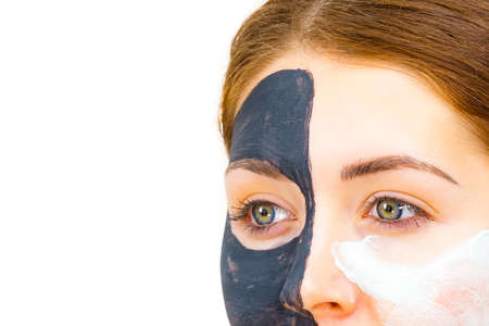 Woman with clay carbo black mask on half face applying white mud to clean skin. Girl taking care of oily complexion. Beauty procedures. Skincare. Banco de Imagens