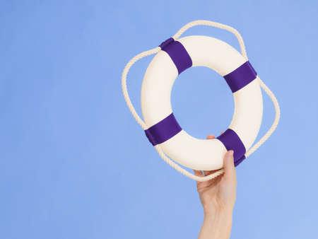 Ręka pokazuje biały niebieski pierścień ratunkowy boja ratunkowa z liny. Sprzęt bezpieczeństwa. Zapobieganie wypadkom i ratownictwo wodne. Zdjęcie Seryjne