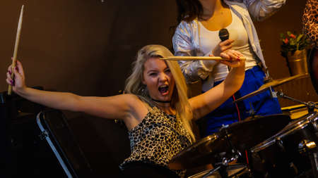 Woman singing while rest of the band playing instruments, performing on stage. Female musicians: drummer and singer