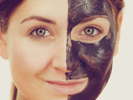 Woman with clay carbo detox black mask on her face. Girl taking care of oily skin complexion. Beauty treatment. Skincare. Stok Fotoğraf