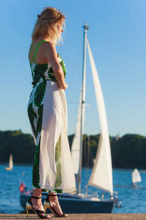 Blonde fashion model against sea. Pretty young adult woman wearing long white green summer dress and high heels shoes relaxing on seaside