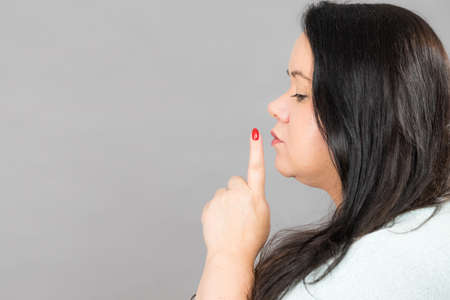 Adult woman asking for silence or secrecy with finger on lips, hush hand gesture, side view on grey, copy space text area Stockfoto