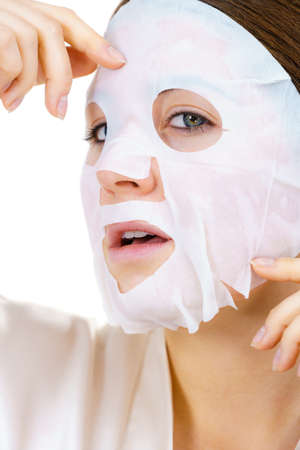 Woman applying sheet mask on her face, on white. Girl taking care of skin complexion. Beauty treatment. Skincare. Stockfoto