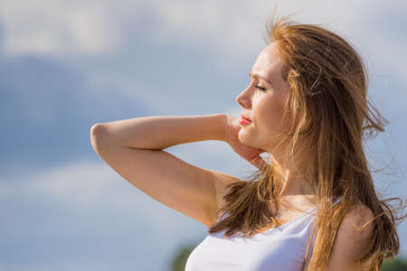 Young woman relaxing outdoor. Female enjoy sunlight against blue sky. Stockfoto