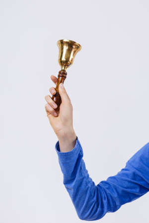 Woman hand wearing blue long sleeve shirt holding old fashioned golden bell.