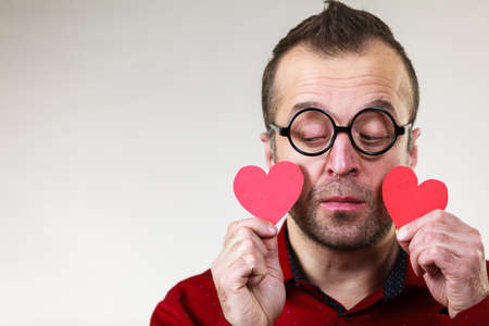 Adult serious man holding two red hearts. Romance love valentines day concept.