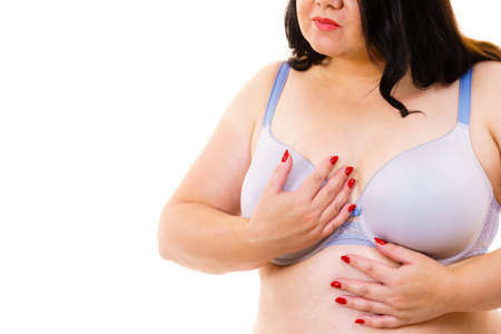 Plus size fat mature woman wearing bra, on white. Female breast in lingerie. Bosom, brafitting and underwear concept.