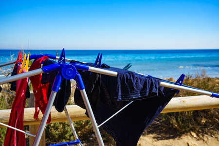 Camping on beach, adventure concept. Clothes hanging to dry on laundry line outdoor against sea. Banque d'images