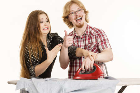 Woman trying to teach her stupid man how to do ironing clothes. Husband being silly.