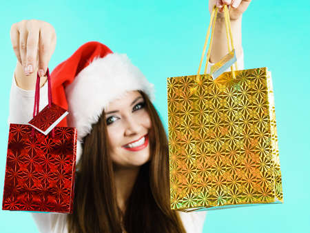 Young brunette woman is happy to give Christmas gifts. Female wearing santa claus hat holding presents festive gift bags, on blue