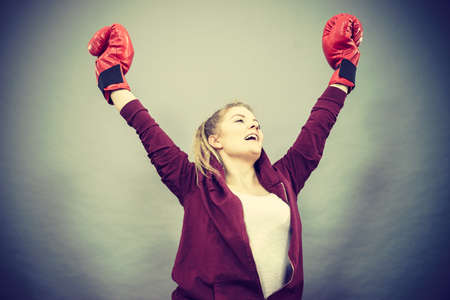 Sporty woman wearing red boxing gloves, winning fight, being motivated feeling relief and happiness. Studio shot on dark background.