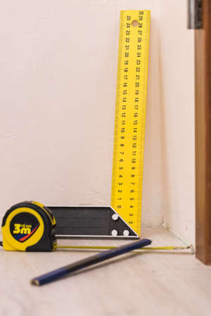 Home renovation concept. Working diy tools. Industrial ruler yellow tape measure, floor panels.