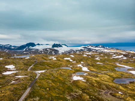 Road through mountain landscape. Snow peaks and glaciers in the distance. National tourist scenic route 55 Sognefjellet Norway. Aerial view 版權商用圖片