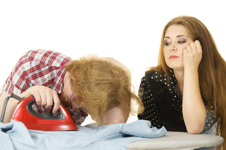 Tired couple while doing household duties. Man and woman being bored ironing clothes.