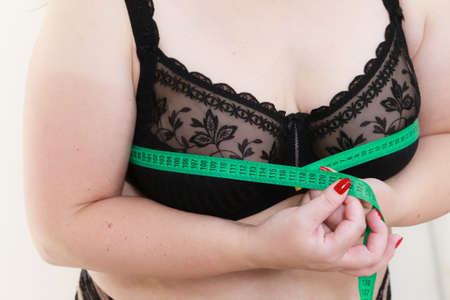 Plus size fat woman wearing black bra using tape measure to check the measurements of her big chest breasts. Closeup part of female body. Bosom, brafitting and underwear concept.