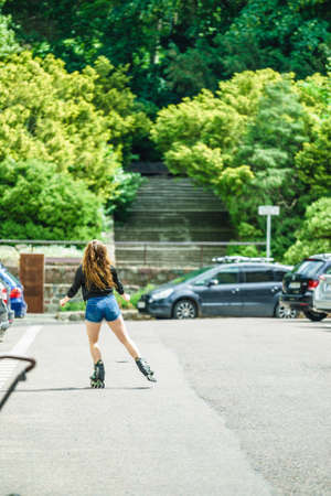 Teenage woman girl riding roller skates during summertime through city having great time.