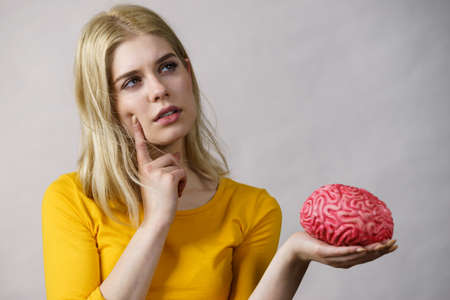 Young woman female student thinking about solving problem, holding fake brain. Imagens