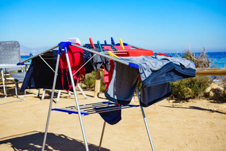 Camping on beach, adventure concept. Clothes hanging to dry on laundry line outdoor against sea. 版權商用圖片