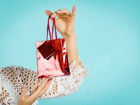 Female holding present red gift bag in hand, on blue