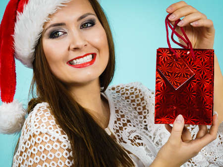 Young adult woman is happy to give Christmas gifts. Female wearing santa claus hat holding present red gift bag, on blue