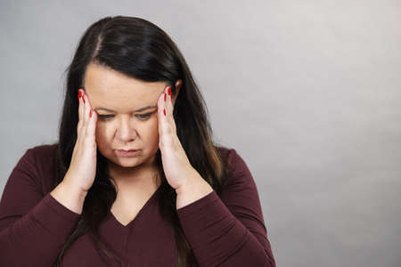 Headache, migraine and stress. Worried plus size adult upset woman suffering from head pain, studio shot on gray.
