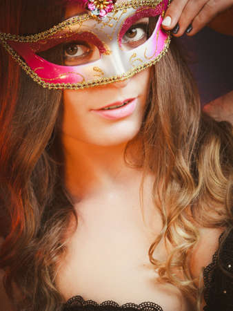 Holidays, people and celebration concept. Closeup woman face with carnival pink feather mask on dark background.