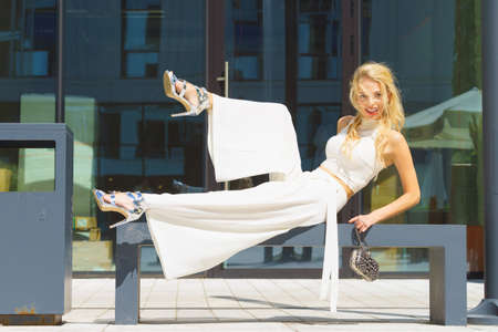 Elegant fashionable woman presenting trendy urban outfit. White crop top and trousers culottes. Outdoor photo session, unusual bizarre pose