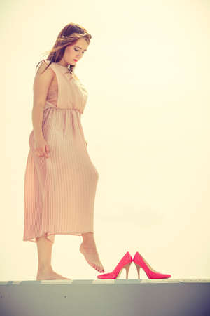Hobby, idyllic aspects of femininity concept. Woman walking on jetty without shoes wearing beautiful long light pink dress.