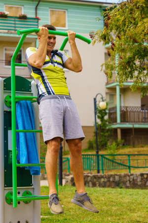 Young handsome man working out in outdoor gym. Sporty guy flexing his muscles doing pull ups on machine. Staying fit and healthy. Reklamní fotografie