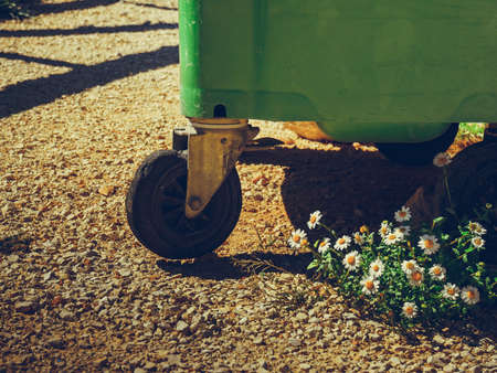 Industrial big garbage bin outdoors on rest stop area and white flowers