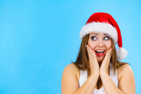 Woman wearing santa claus hat surprised expression, on blue with copy space. Christmes time. Фото со стока