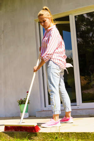 Female adult young woman using big broom to clean up backyard patio Stok Fotoğraf